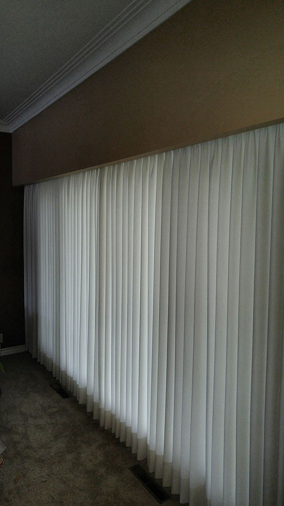 a long row of floor-length soft shades covering a window