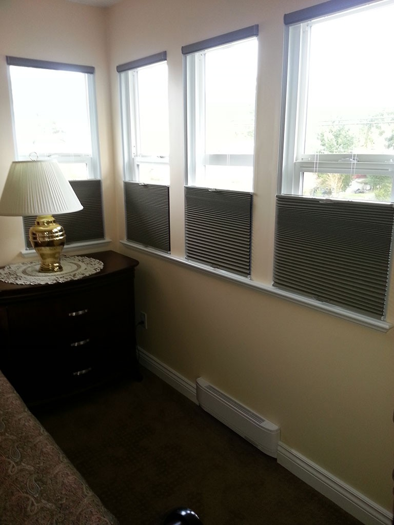 soft shades covering the bottom portions of 4 bedroom windows and letting light in through the top