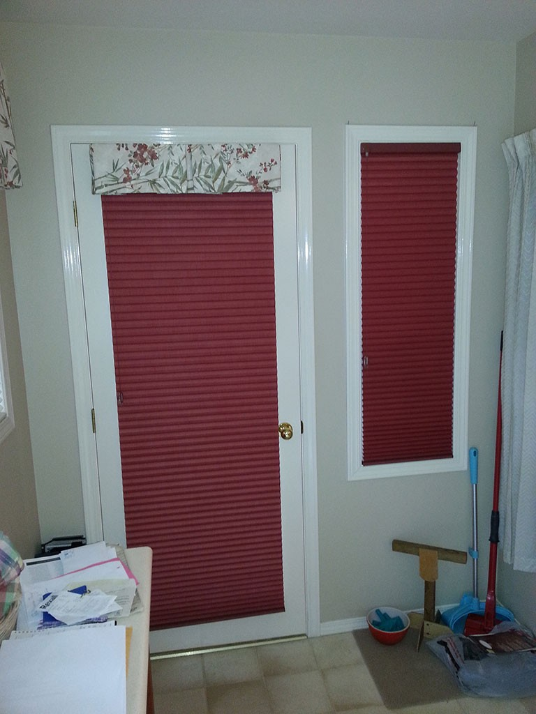matching soft red shades completely blocking the light from a glass door and adjacent window