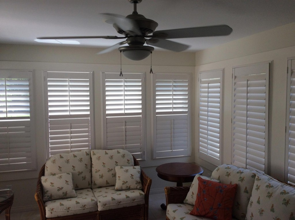 white shutters in a living room with large windows, plush white couches, and a ceiling fan