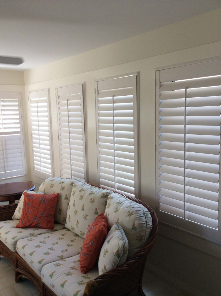 white shutters in a living room with large windows a plush white couch
