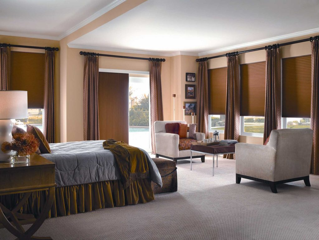 A bedroom with matching brow horizontal shades on the windows and vertical shades on the patio doors