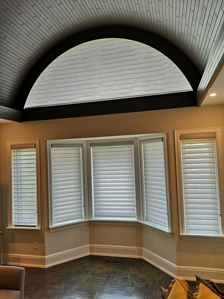 soft shades covering five rectangular windows and one large half circle window above